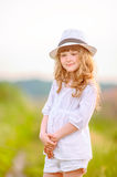 Young beautiful girl posing in a hat near the field. The young beautiful girl posing in a hat near the field stock photo