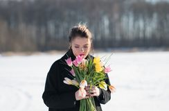 Young beautiful girl posing outside in the winter with a bouquet of tulips in a black royalty free stock images