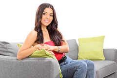 Young beautiful girl posing seated on a sofa Stock Photos