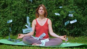 Young beautiful girl practices yoga in nature. Money 100 dollar bill is flying from the sky. Young beautiful girl practices yoga in the park, sitting on a stock video