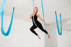 Young beautiful girl practicing aerial yoga in gym. royalty free stock photography