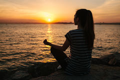 Young beautiful girl practicing yoga and meditation on the rocks next to the sea at sunset. Sport. Yoga. Meditation. Young beautiful girl practicing yoga and Stock Photos