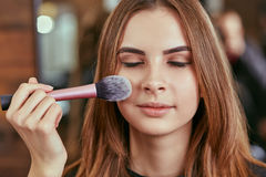 Young, beautiful girl put on make-up in a beauty salon Royalty Free Stock Photos