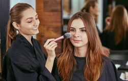 Young, beautiful girl put on make-up in a beauty salon Stock Photography