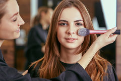 Young, beautiful girl put on make-up in a beauty salon Royalty Free Stock Photography