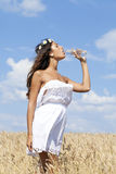 Young beautiful girl quenches thirst Royalty Free Stock Photos
