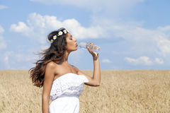 Young beautiful girl quenches thirst Stock Image