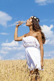 Young beautiful girl quenches thirst Stock Images