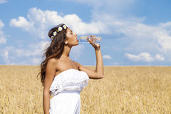 Young beautiful girl quenches thirst Royalty Free Stock Images