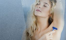 Young girl with a razor in hand shaves after taking a shower on an isolated background.Concept beauty and skin care royalty free stock photography