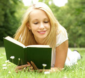A young and beautiful girl is reading a book Royalty Free Stock Images
