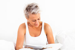 Young beautiful girl reading a book stock image