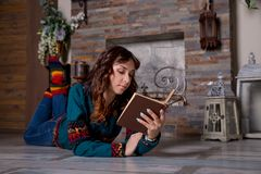 Young beautiful girl is reading a book near a fireplace, wrapped in a warm woolen blanket, socks. Cozy evening in chalet. Young beautiful girl is reading a book royalty free stock images