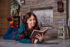 Young beautiful girl is reading a book near a fireplace, wrapped in a warm woolen blanket, socks. Cozy evening in chalet. Young beautiful girl is reading a book stock photography