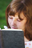 Young beautiful girl reading a book outdoor Stock Photo