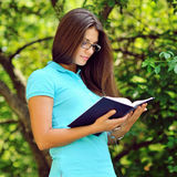 Young beautiful girl reading book in a park Stock Photos