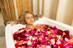 Young beautiful girl receives taking bath with rose petals in spa Stock Images