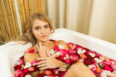 Young beautiful girl receives taking bath with rose petals in spa. Young beautiful girl receives milk bath with rose petals in spa salon Royalty Free Stock Photography