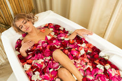 Young beautiful girl receives taking bath with rose petals in spa. Young beautiful girl receives milk bath with rose petals in spa salon Stock Photo