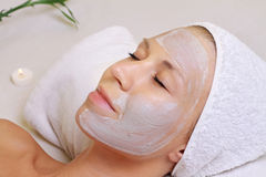 Young beautiful girl receiving clay facial mask in spa Royalty Free Stock Image