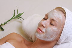Young beautiful girl receiving clay facial mask in spa beauty salon.  Skin care, Beauty treatments. Stock Photography