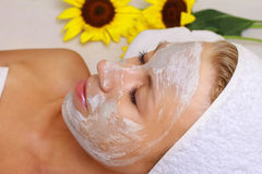 Young beautiful girl receiving clay facial mask in spa beauty salon.  Skin care, Beauty treatments. Stock Image
