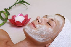 Young beautiful girl receiving clay facial mask in spa Royalty Free Stock Photo