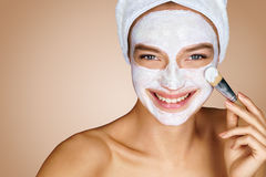 Young beautiful girl receiving cosmetic facial mask Stock Image