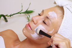 Young beautiful girl receiving facial mask in spa beauty salon.  Skin care, Beauty treatments. Stock Photography