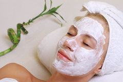 Young beautiful girl receiving  facial mask in spa beauty salon.  Skin care, Beauty treatments. Stock Photos