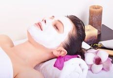 Beautiful girl receiving pink facial mask Royalty Free Stock Image