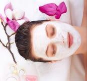 Young beautiful girl receiving pink facial mask Stock Image