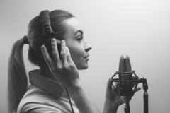 Young beautiful girl records vocals, radio, voiceover tv, reads poetry, blog, podcast in the studio on the studio microphone with stock photos