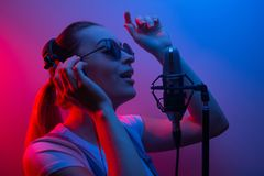 Young beautiful girl records vocals, show business, DJ, party, pop music royalty free stock photo