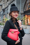 Young beautiful girl with red bag, wearing a black hat and leath Stock Photos