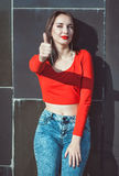 Young beautiful girl in red blouse showing thumbs up Royalty Free Stock Image