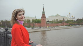 Young beautiful girl in a red coat posing on the bridge on the background Red Square, Moscow Kremlin, Russia stock video
