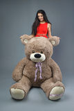 Young beautiful girl in red dress with big teddy bear soft toy happy smiling and playing on grey background Stock Photography