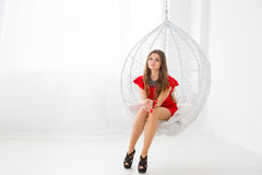 Young beautiful girl in red dress resting in a sphere-like decorative swing. Elegant and cozy place to relax Stock Image