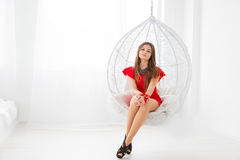 Young beautiful girl in red dress resting in a sphere-like decorative swing. Elegant and cozy place to relax Royalty Free Stock Photo