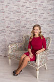 Young beautiful girl in red dress sitting in an armchair and looking at camera Stock Images