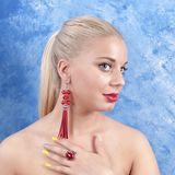 Young beautiful girl in red earrings on an abstract background. Stock Image