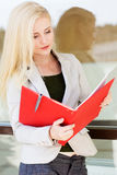 Young beautiful girl with a red folder and books Stock Photos