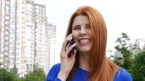 Young beautiful girl with red hair in the city, dials a phone number, talking on a mobile phone and smiling. Young beautiful girl with red hair in the city stock footage