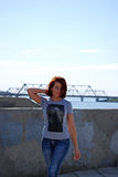 The young beautiful girl with red hair poses against the background of the river and the railway bridge Stock Photography