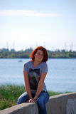 The young beautiful girl with red hair poses against the background of the river and the railway bridge Royalty Free Stock Image