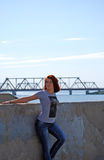 The young beautiful girl with red hair poses against the background of the river and the railway bridge Stock Image