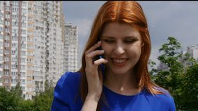 Young beautiful girl with red hair talking on a mobile phone and smiles. Very happy in the city. Young beautiful girl with red hair talking on a mobile phone stock video footage