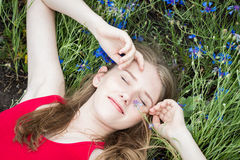 Young beautiful girl relaxing in the meadow of cornflowers Stock Photo
