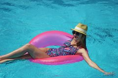 Young beautiful girl relaxing and swimming in the blue swimming pool with a pink circle closeup stock photography